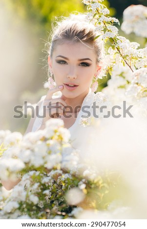 Blonde woman in flowers. beautiful happy blonde woman in the park on a warm summer day. Woman in bloom. - stock photo