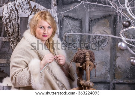 Blonde woman in Russian traditional dress with knitting needles in her hands