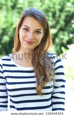 Blonde woman in the park looking to the camera - stock photo