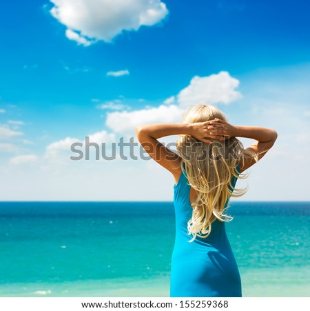 Blonde Woman in Turquoise Dress Standing at Sea. Summer Vacation. - stock photo