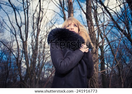 blonde woman in warm coat with fur in the forest, cold winter day