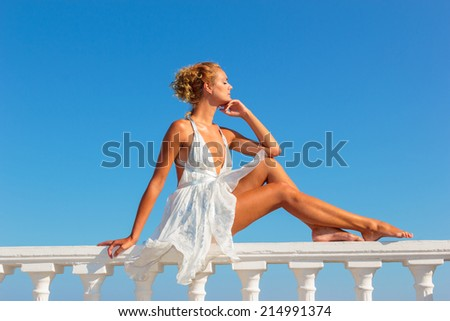Blonde woman in white dress by the sea in the summer time