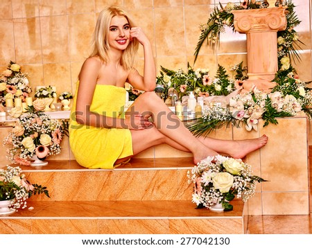Blonde woman in yellow towel relaxing at flower water spa. - stock photo