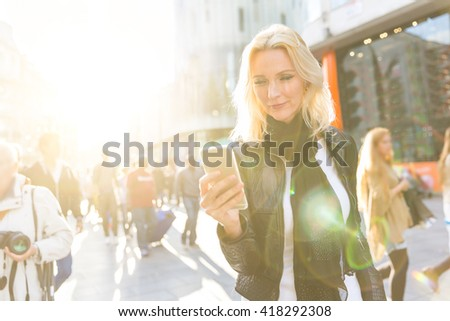 Blonde woman looking at smart phone in London at sunset. She is on her early forties, she looks candid and spontaneous. Backlight shot with blurred people on background.