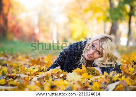 blonde woman lying in the autumn park