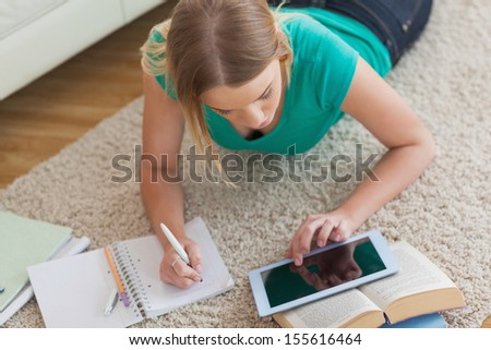 Blonde woman lying on floor using tablet to do her assignment at home in living room - stock photo