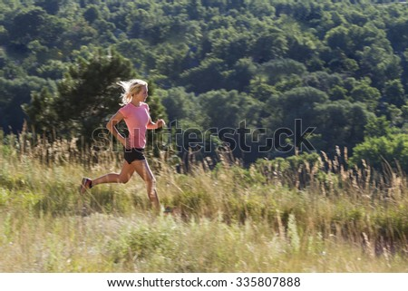 Blonde woman on mountain trail run with pine forest vista shot from side with blur pan. - stock photo