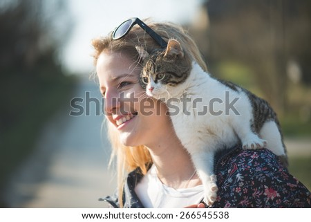 Blonde woman playing with her adorable cat - stock photo