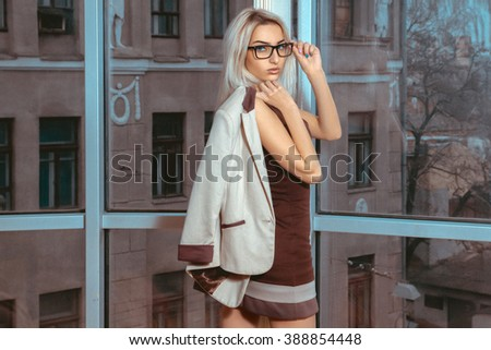Blonde woman posing near the large window with city views. Business woman posing. City views behind the window in the office. Business concept. - stock photo