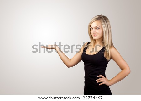 blonde woman presenting hand, copyspace on left - stock photo