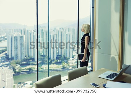 Blonde woman proud CEO is holding touch pad and looking in office window with cityscape, while is standing in conference room near table with open laptop computer during her business trip in New York - stock photo