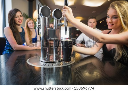 Blonde woman pulling a pint of stout in front of her friends at a bar - stock photo