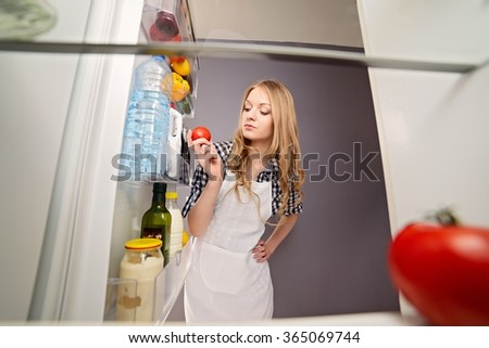 Blonde woman pulls tomato from the refrigerator. Dressed in a plaid shirt and white apron. Photo taken from the inside of the refrigerator - stock photo