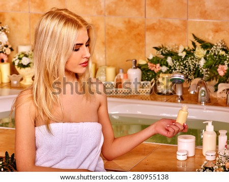 Blonde woman relaxing at flower water spa. Holding bottle. - stock photo