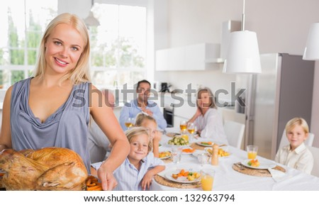 Blonde woman showing the roast turkey with her family behind her - stock photo