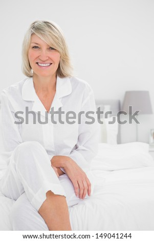 Blonde woman sitting cross legged  in her bedroom smiling at camera