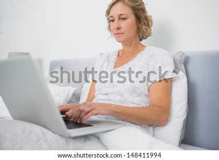 Blonde woman sitting in bed using laptop at home in bedroom