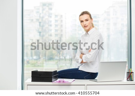 blonde woman sitting on her office - stock photo