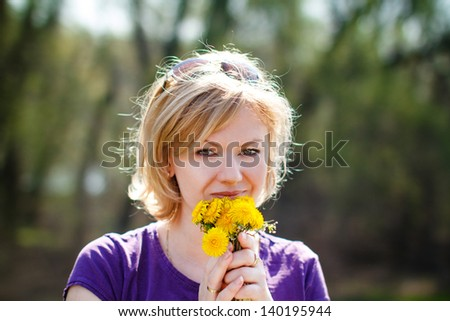 Blonde woman smell dandelion, outdoors - stock photo
