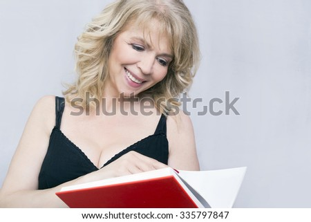 Blonde woman smiling and reading a book