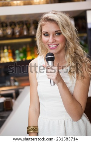 Blonde woman smiling while singing into a microphone at the nightclub - stock photo