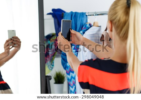 Blonde woman standing near wardrobe rack full of clothes and mirror making selfie with cellphone in new dress. Shopping and consumerism or stylist concept. Nothing to wear and hard to decide concept - stock photo