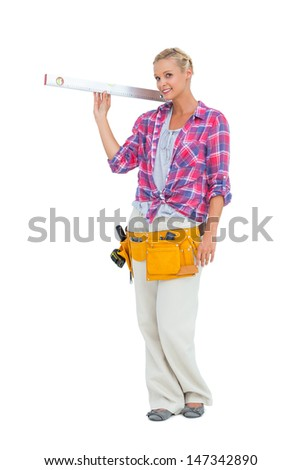 Blonde woman standing while holding a spirit level on white background - stock photo