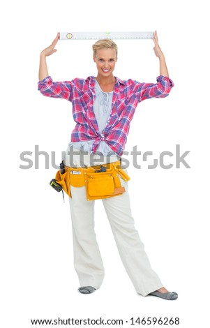 Blonde woman standing while putting a spirit level on her head on white background - stock photo