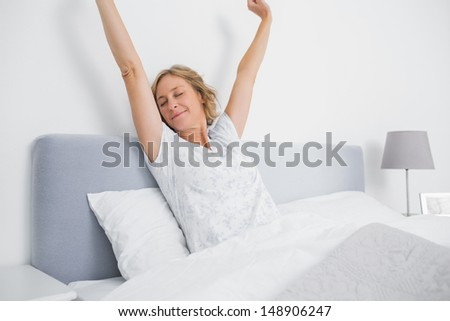 Blonde woman stretching and smiling in bed in the morning in bedroom at home