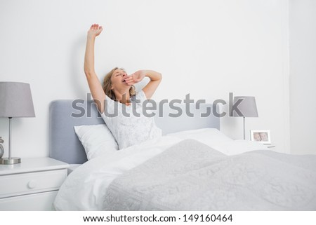Blonde woman stretching and yawning in bed in the morning in bedroom at home - stock photo