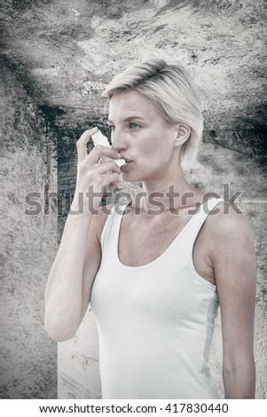 Blonde woman taking her inhaler against image of room corner - stock photo