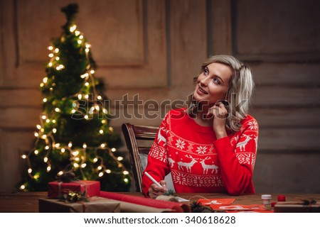 blonde woman thinking about words on christmas postcard - stock photo