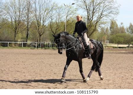 Blonde woman trotting on beautiful latvian breed horse - stock photo