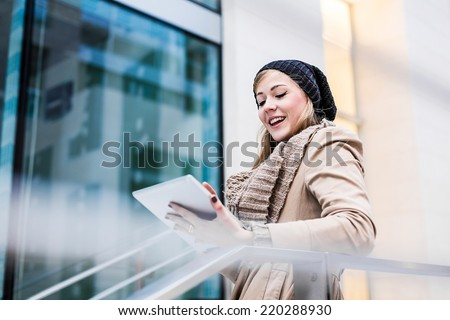 Blonde woman using a digital tablet outdoor - stock photo