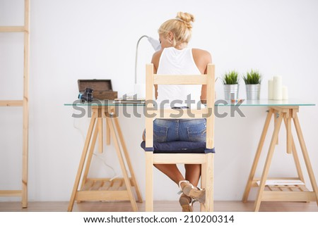 Blonde woman using her laptop in her workspace. View from behind - stock photo