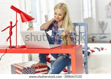 Blonde woman using laptop computer at home, smiling, drinking tea. - stock photo