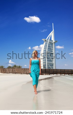 Blonde woman walking along the beach in the front of the Burj Al Arab hotel in Dubai - stock photo