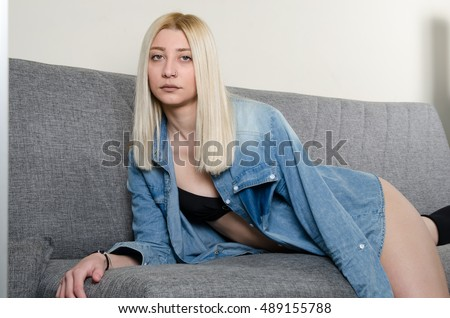 Blonde woman wear stockings socks, open shirts and underwear sitting on the sofa