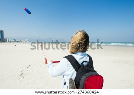 Blonde woman wearing a backpack flying a kite at the sandy sunny beach - stock photo