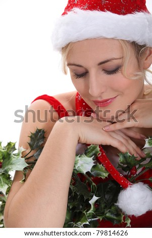 blonde woman wearing a Christmas costume hugging holly and having an expression of purity