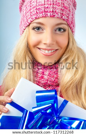 blonde woman wearing knitwear  holding gift box over blue background - stock photo