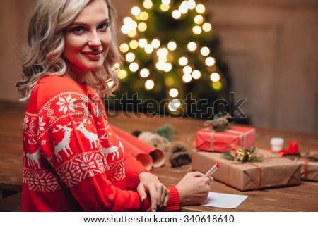 blonde woman wearing red sweater write on christmas postcard
