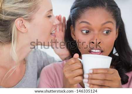 Blonde woman whispering secret to her friend who is surprised - stock photo