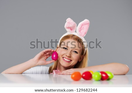 Blonde woman with bunny ears and easter eggs - stock photo