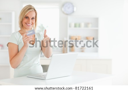 Blonde woman with credit card and notebook holding thumb up in the kitchen