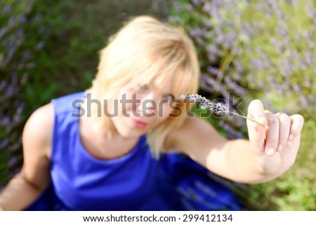 Blonde woman with elegant blue dress sitting on a field of lavender and watching a bunch of lavender flowers in her hand. Focus on the flower. Concept of nature in contact with people. - stock photo