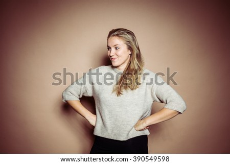 Blonde woman with grey wool jersey posing in front of beige background in studio with vibrant contrasty light - stock photo