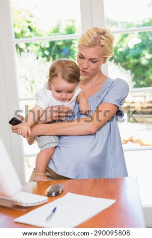 Blonde woman with his son using laptop in the office - stock photo