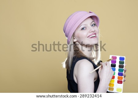 Blonde woman with paint and brush on beige background - stock photo