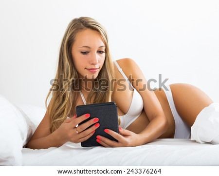Blonde woman with tablet of eBook lying in her bed at home  - stock photo